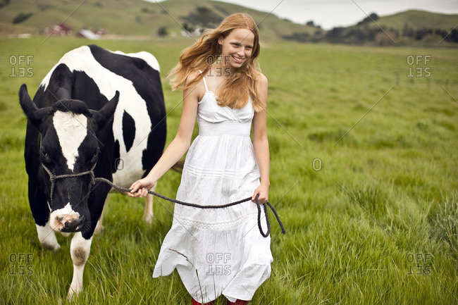 Young woman leading a cow through a field.