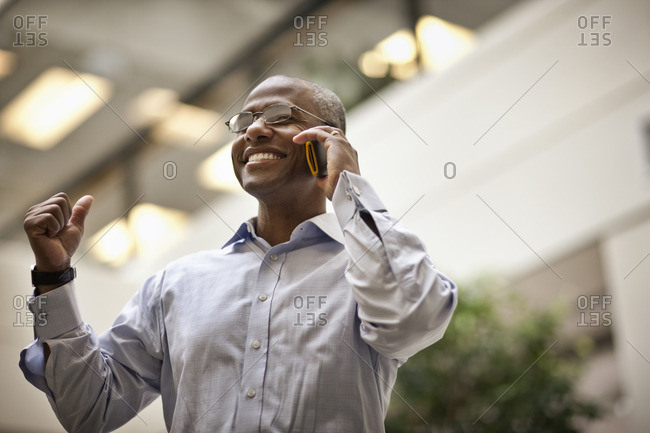 Businessman smiling while talking on his cellphone.