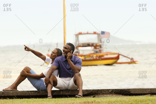 Couple sitting at the edge of the water.