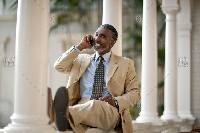 Businessman smiling and talking on his cellphone.