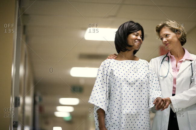 Doctor walking with a patient down a hospital corridor.