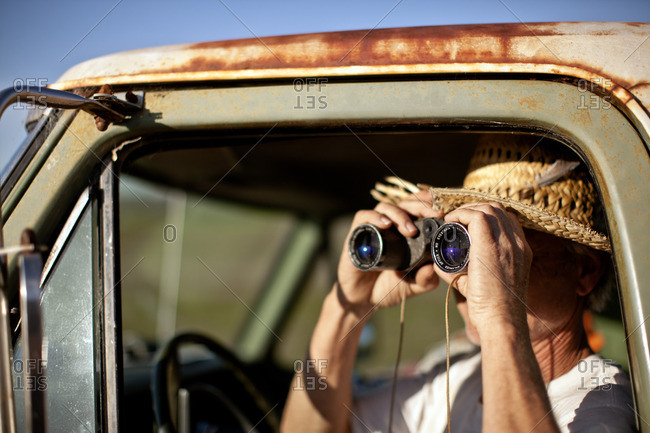 Man looking through binoculars from his truck.