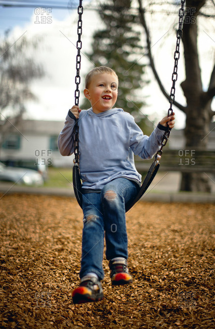 Young boy swinging on a playground swing.