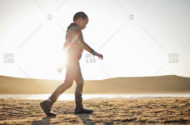Young boy in a wetsuit walking on the beach.