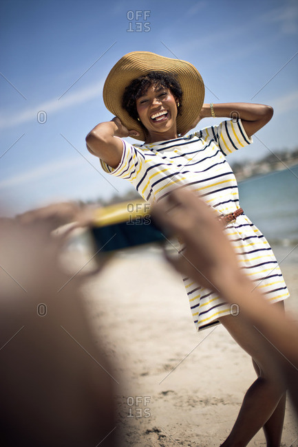 Young woman posing for a photograph on the beach.