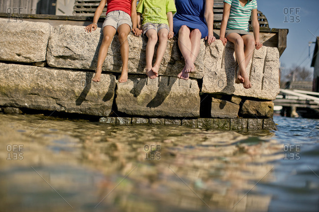 Group of people sitting at the edge of a stone pier.