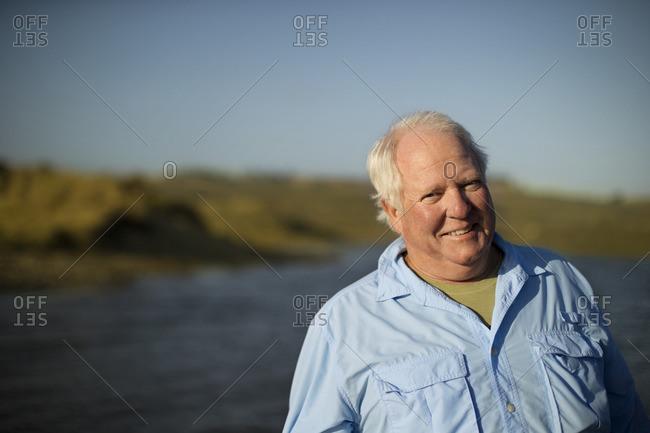 Smiling senior man standing by a lake.