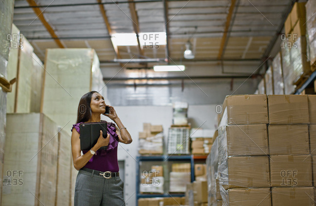 Businesswoman in a storeroom filled with boxes.