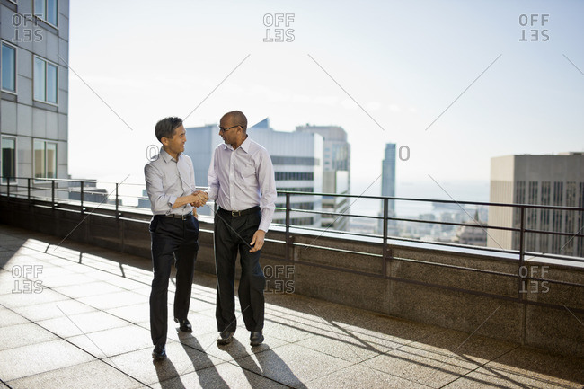 Two businessmen shaking hands on an office balcony.