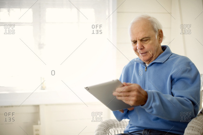 Senior man sitting using a tablet computer.