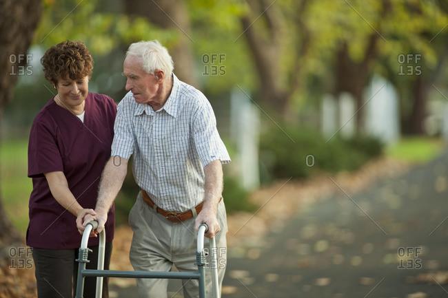 Nurse helping a senior man while walking along a treelined footpath.