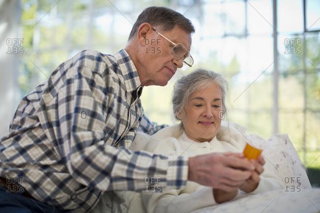 Senior couple reading a medication bottle.
