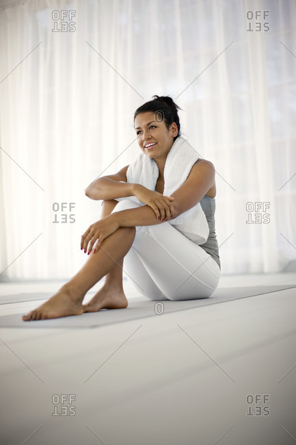 Young woman sitting on a mat during an exercise class.