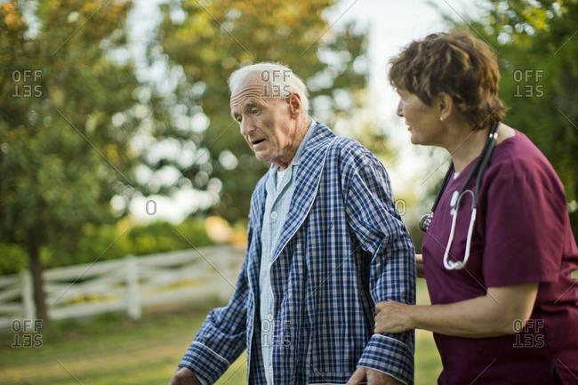 Senior man and his nurse walking in the garden.