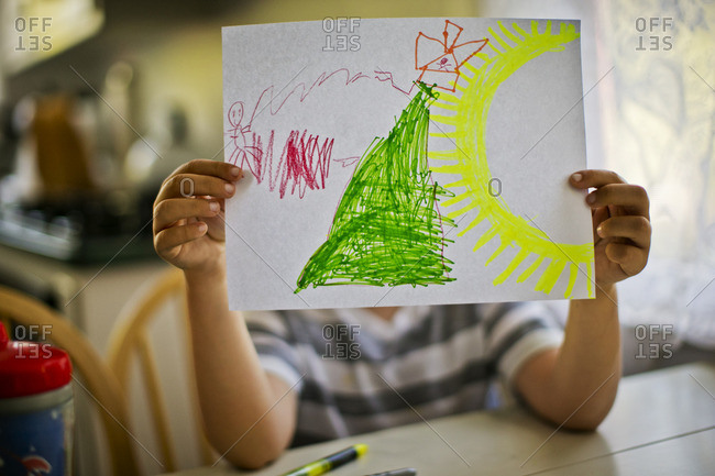 Child showing a picture he has drawn.