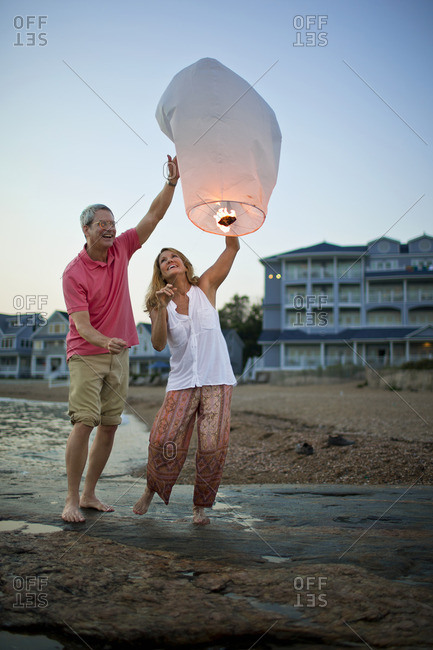 Couple letting a Chinese lantern go on the beach.