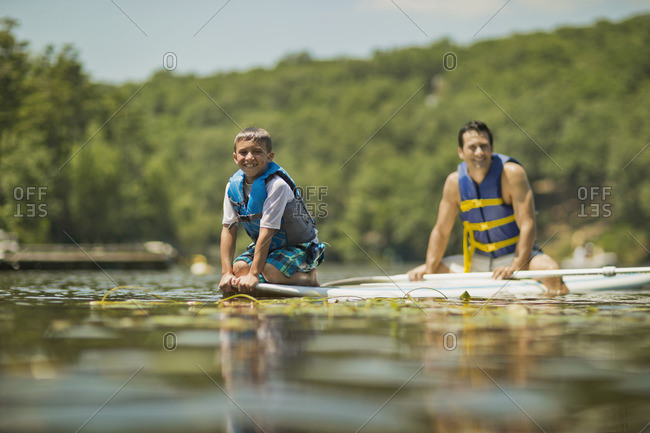 Father and son paddleboarding together.