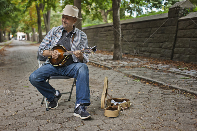 Busker playing a banjo on a treelined street.