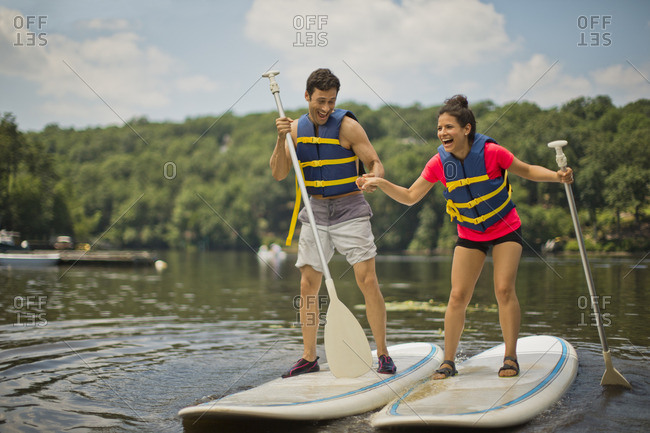 Young couple paddleboarding together.