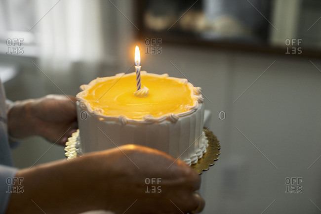 Person carrying a birthday cake with a single candle.