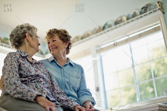 Senior woman and her daughter sitting side by side.