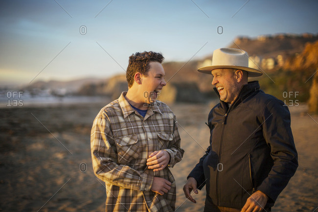 Father and his teenage son laughing together on the beach.