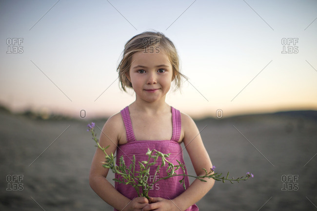 Young girl holding purple flowers on the beach.