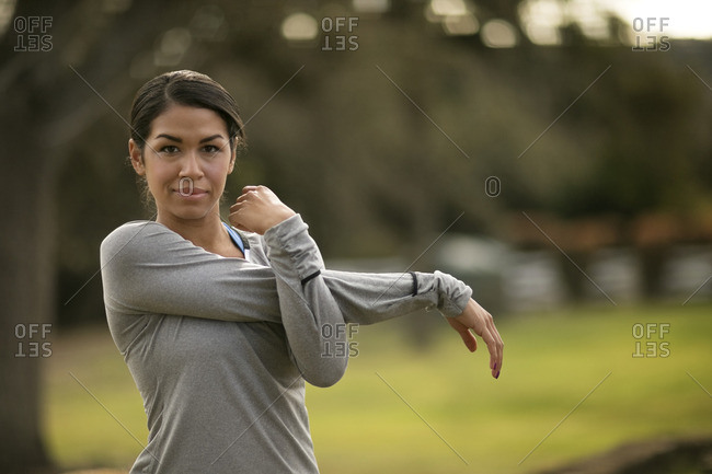 Young woman stretching before exercising in the park.
