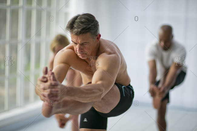 Man standing on one leg during a yoga class.