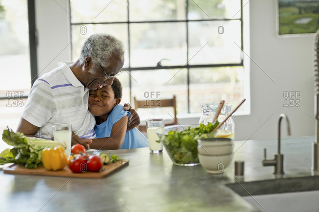 Grandfather and grandson share a hug while preparing lunch.