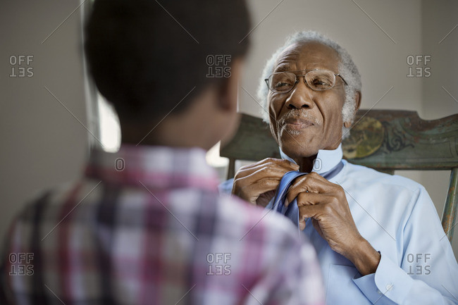 Senior man demonstrating how to tie a tie to his grandson.