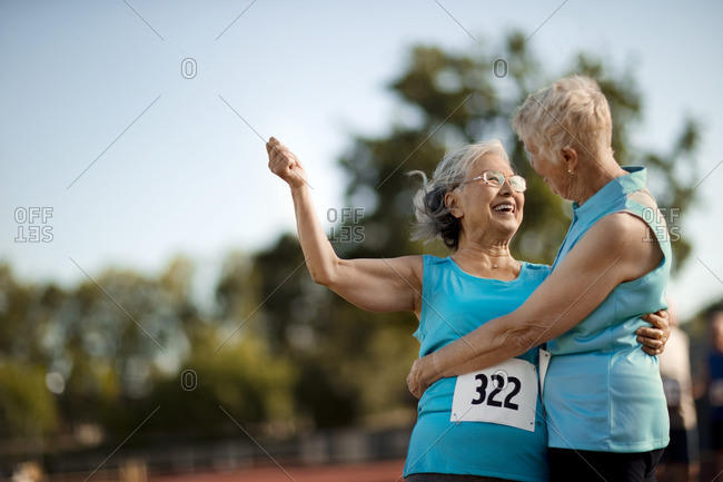 Two senior women hugging after a sports race.