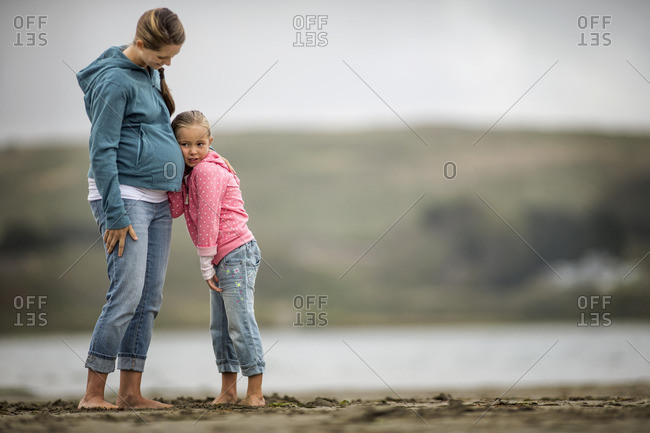 Young girl resting her head on her pregnant mother's belly.