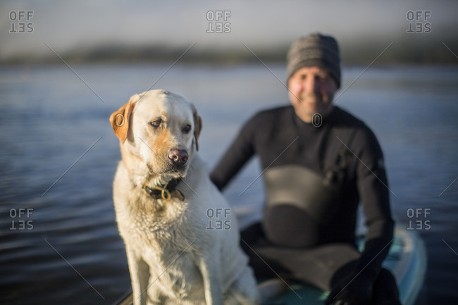 Man paddleboarding with his dog.