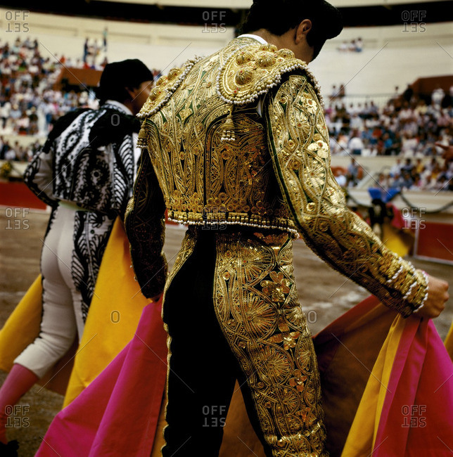 Matadors holding their flags in the bull ring.