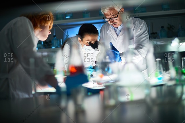 Confident scientists in white coats standing at the table with laboratory glassware