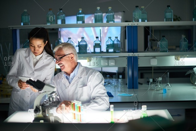 Senior silver-haired male scientist sitting at the table while his young female colleague showing him results of conducted experiment on digital tablet
