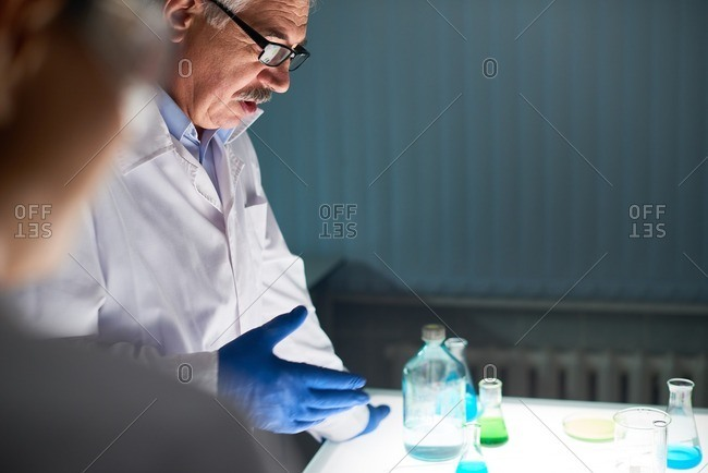 Profile view of senior chemistry teacher in eyeglasses standing at the laboratory table and explaining experiment to his pupils