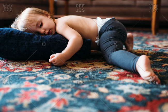 Toddler girl lying on pillow on the floor at home.