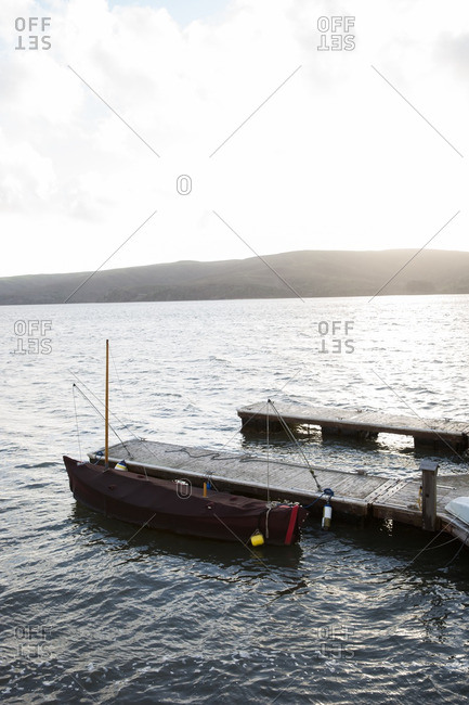 Small covered boat tied to dock on Tomales Bay