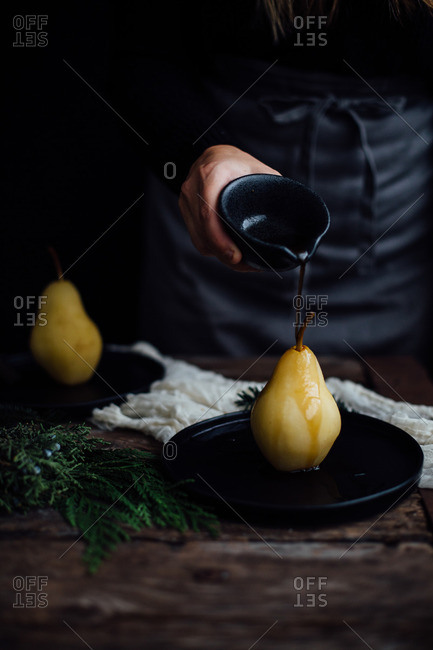 Woman pouring syrup on a pear