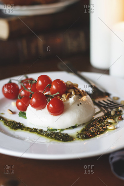 Fresh mozzarella served with cherry tomatoes, pine nuts, and pesto
