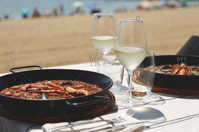 Seafood paella served with white wine outdoors