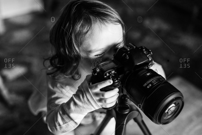 Little girl playing with DSLR camera