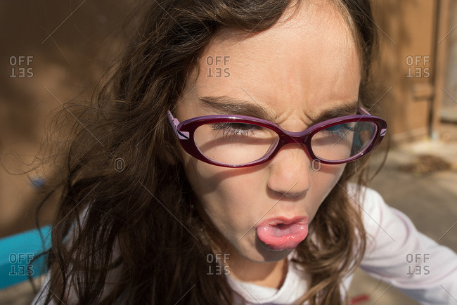 Girl with curly hair and glasses sticking her tongue out
