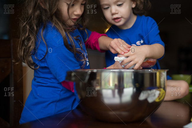 Two little girls putting whipped cream into a bowl