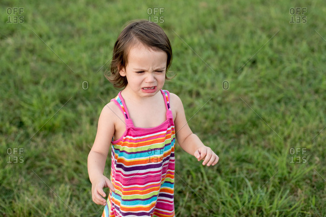 Toddler girl in striped dress throwing a fit
