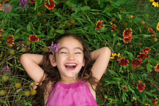 Little girl lying in the grass by colorful flowers