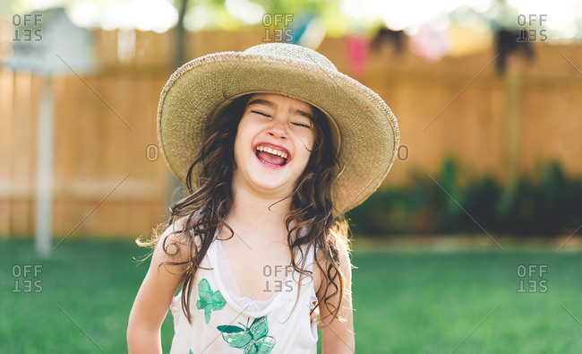 Young girl wearing hat laughing