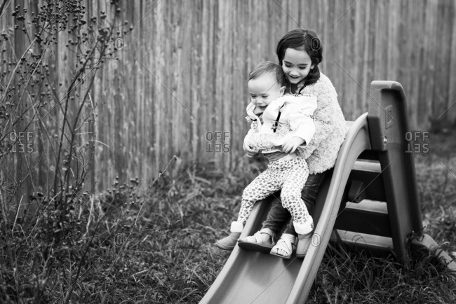 Girl holding her toddler sister while going down a slide